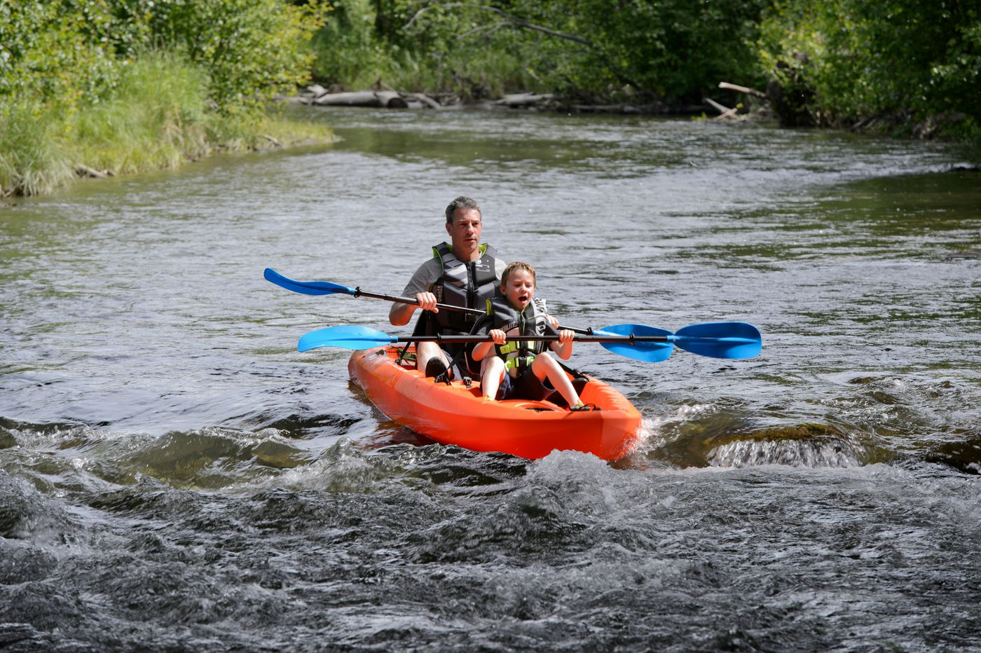 David Brust floats into a riffle with his 6-year-old son Clark Jacobs on Campbell Creek under the Seward Highway on July 1. (Marc Lester / ADN)