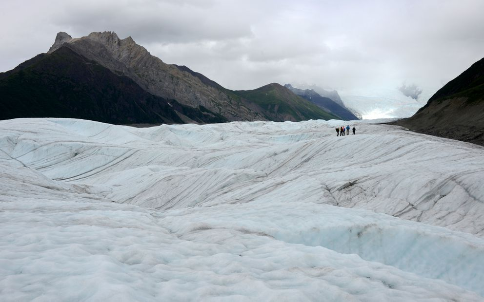 Guided visitors explore Root Glacier near Kennecott. The Stairway Icefall is at right in the distance, and Donoho Peak is at left. The glacier joins the Kennicott Glacier near the Kennecott Mine site in Wrangell St. Elias National Park and Preserve. (Erik Hill / ADN archive 2015)