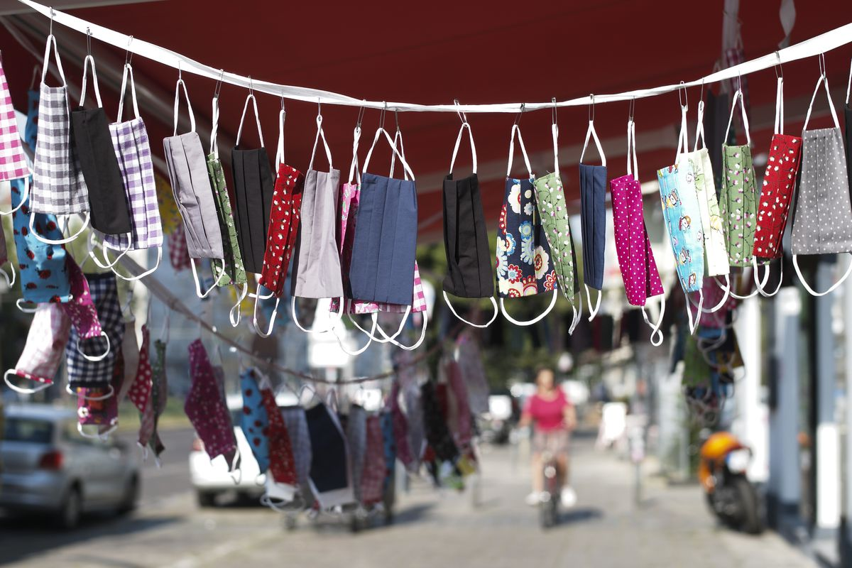 Protective masks in cotton sewn displayed for sale in front of a tailor shop in Berlin, Germany, Thursday, Aug. 13, 2020. In public transport, shops and public buildings at the German capital, it is essential to wear a face mask to protect against the coronavirus. (AP Photo/Markus Schreiber)