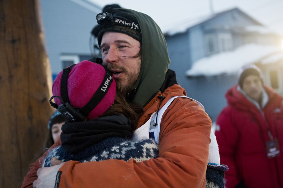 Brent Sass hugs Ida Mortensen under the burled arch of the Iditarod Trail Sled Dog Race on March 18, 2020, in Nome. (Marc Lester / ADN)