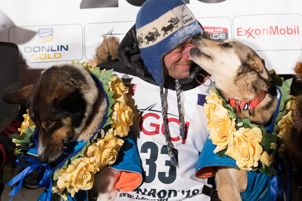 Joar Leifseth Ulsom gets a kiss from his lead dog Olive after he won the Iditarod early Wednesday morning, March 14, 2018 in Nome. His other lead dog is Russeren. (Loren Holmes / ADN)