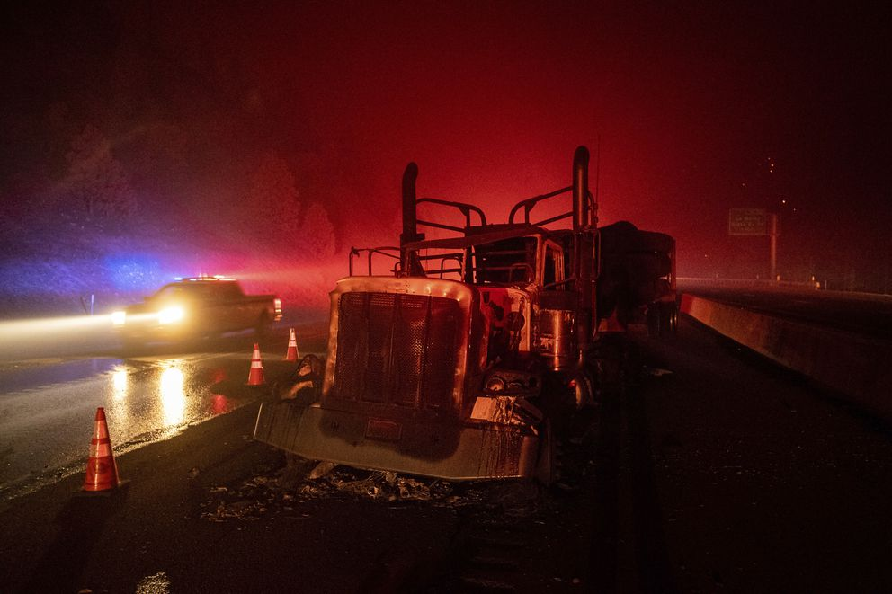 A scorched logging truck rests on Interstate 5 as the Delta Fire burns in the Shasta-Trinity National Forest, Calif., near Shasta Lake on Wednesday, Sept. 5, 2018. Parked trucks lined more than two miles of the highway as both directions remained closed to traffic. (AP Photo/Noah Berger)