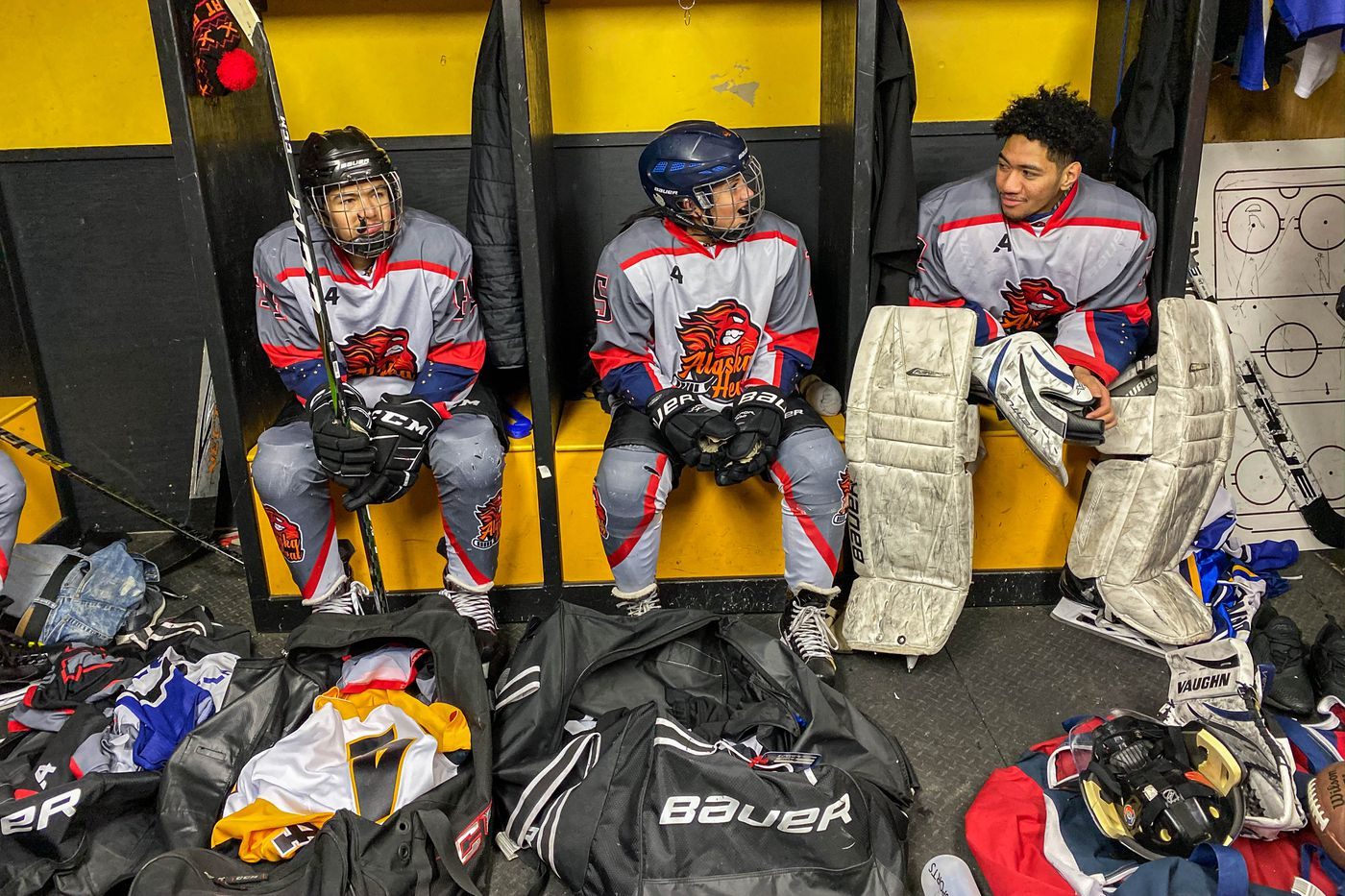 From left, forward Richard Charlie of Tok, defenseman Cassidy Matthews of Glennallen and goalie Charlie Taui of Utqiagvik recover between periods. (Loren Holmes / ADN)