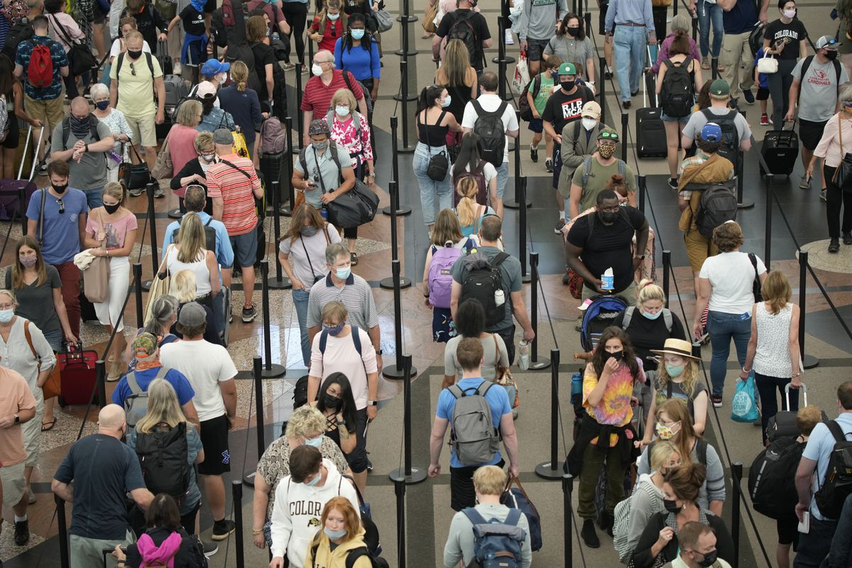 Travelers queue up in long lines to pass through a security checkpoint at Denver International Airport, Wednesday morning, June 16, 2021. (AP Photo/David Zalubowski)