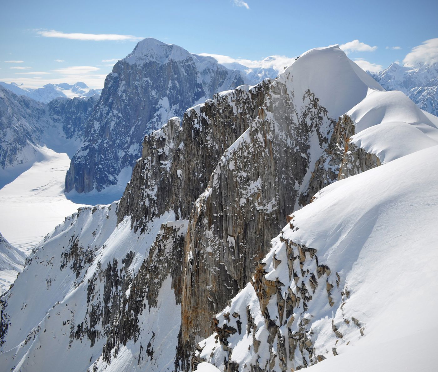 Vertical granite walls drop down from the south side of Root Canal Glacier. Our ski run and campsite were on the gentle, snowy slope on the right of this formation. In the background is 9,945-foot Mount Dickey. Photographed on Tuesday, May 14, 2019. (Vicky Ho / ADN)