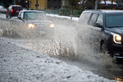 Vehicles kick up water on Spenard Road on December 4, 2017. Rain and temperatures in the 40s hit the Anchorage area Monday. (Marc Lester / ADN)