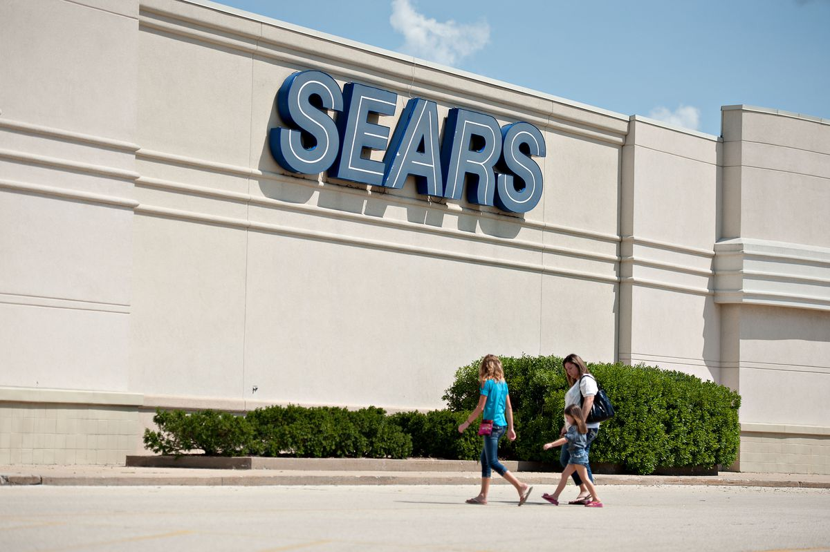 a 2013 photo shows shoppers walking toward a Sears store in Peoria, Illinois. Getting long-struggling Sears to stop bleeding cash has been about as easy as closing the U.S. military prison in Cuba, according to Chief Executive Officer Edward Lampert. (Bloomberg photo by Daniel Acker)