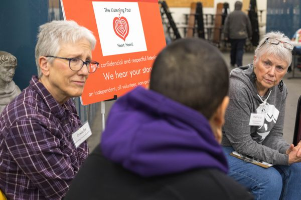 Volunteers Sandy Morris, left, and Patricia Kennish listen to a client at the listening post at Brother Francis Shelter on Tuesday, Dec. 11, 2018. The volunteers, who are not counselors, sit and listen to people who need to talk. (Loren Holmes / ADN)
