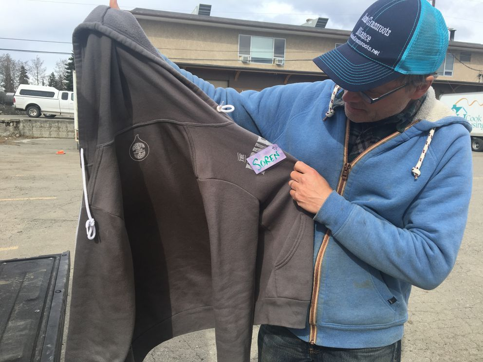 Soren Wuerth, an organizer with Alaska Grassroots Alliance, holds up a sweatshirt that he said was drenched in bear spray or pepper spray Saturday. (Tegan Hanlon / ADN)