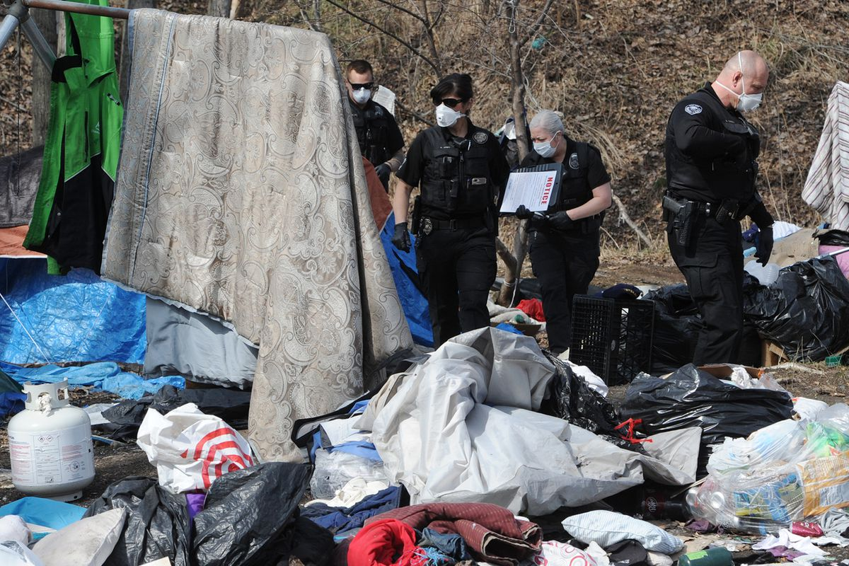 Officers with Anchorage's community action policing team informed people at an illegal homeless camp at Third Avenue and Ingra Street on Thursday, April 30, 2020, that they should clear out before the camp is abated in 10 days. (Bill Roth / ADN)