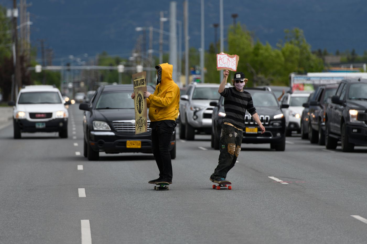 Skateboarders slow traffic on Northern Lights Boulevard Saturday. (Marc Lester / Anchorage Daily News)