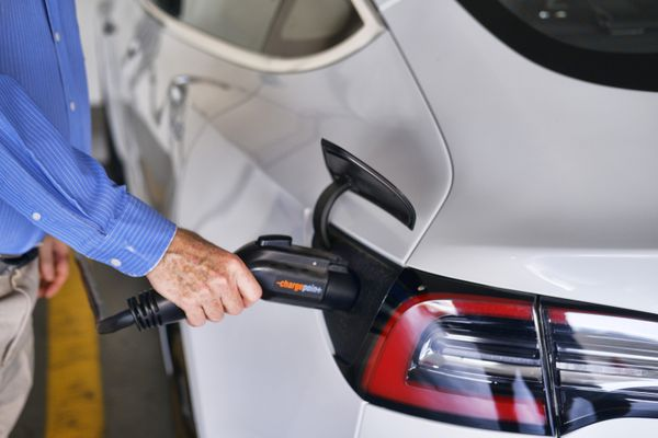 FILE - In this Oct. 16. 2019, file photo a driver plugs in the Charge Point electric plug into his Tesla car at a parking garage in downtown Los Angeles. Experts expect most new cars sold in 2030 to be electric. The Biden administration promised 550,000 charging stations to help with the transition to electric cars.(AP Photo/Richard Vogel, File)