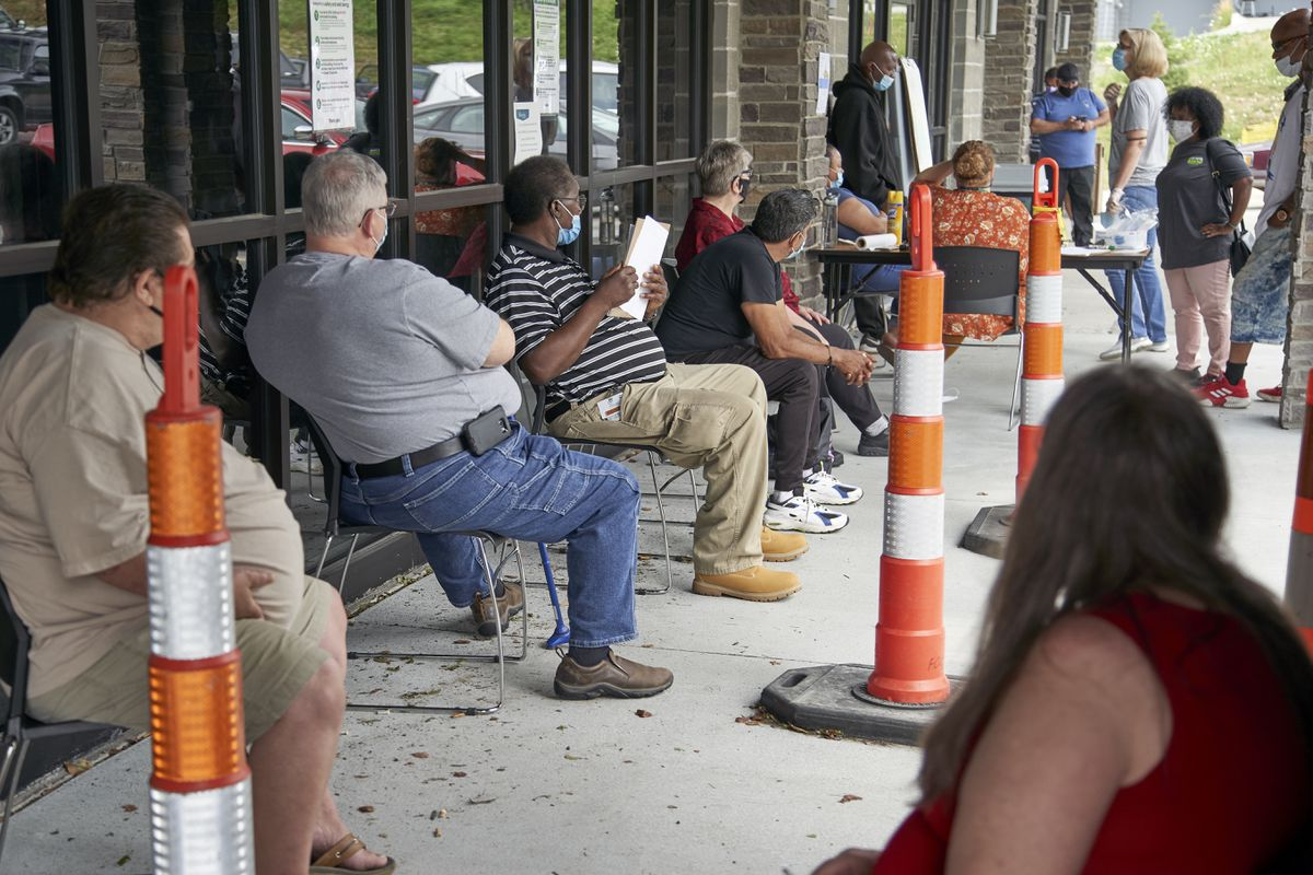 Job seekers exercise social distancing as they wait to be called into the Heartland Workforce Solutions office in Omaha, Neb., Wednesday, July 15, 2020. (AP Photo/Nati Harnik)