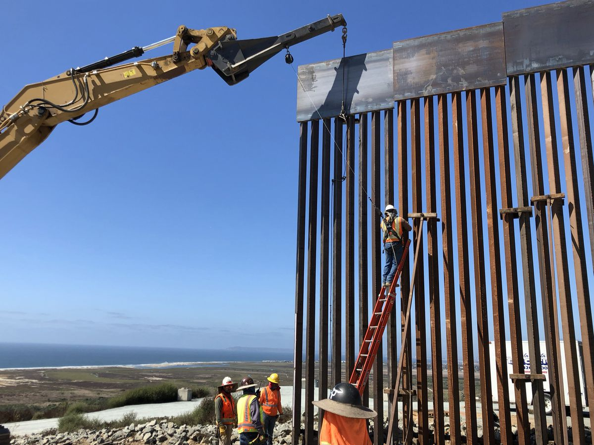 Workers install panels of steel bollard fencing along the U.S.-Mexico border. (Washington Post photo by Nick Miroff)