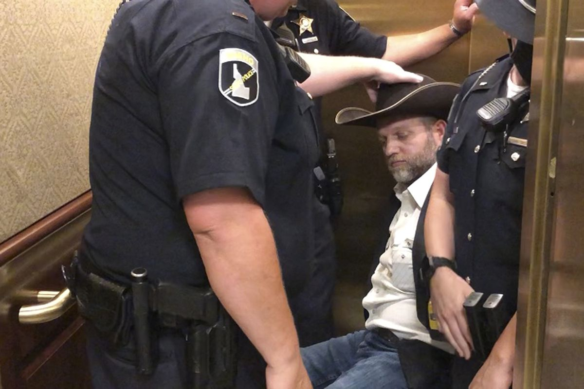 This image taken from video shows anti-government activist Ammon Bundy, rear, being wheeled into an elevator in a chair following his arrest at the Idaho Statehouse in Boise, Idaho, Tuesday, Aug. 25, 2020. Authorities arrested Bundy after he refused to leave a meeting room where a few hours earlier angry protesters forced out lawmakers. (AP Photo/Keith Ridler)