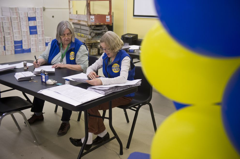 Election workers Gail Loken, left, and Denise Martin look at damaged ballots at Anchorage's Election Center after the 2019 vote-by-mail municipal election. (Marc Lester / ADN archive)