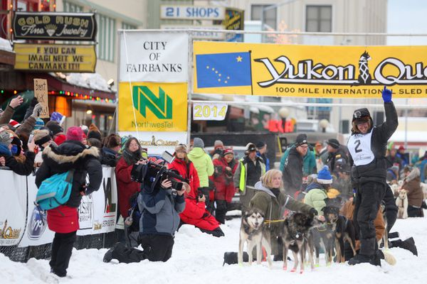 Brent Sass of Eureka, Alaska, waves to the crowd as he gets ready to leave the starting line of the Yukon Quest International Sled Dog Race on Saturday, Feb. 1, 2014, in downtown Fairbanks. This year's Quest start is being moved to next to the Morris Thompson Cultural Center to avoid jumble ice.