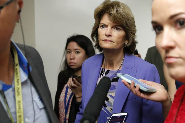 Sen. Lisa Murkowski, R-Alaska, walks on Capitol Hill, Wednesday, Oct. 3, 2018 in Washington, as reporters ask her questions. (AP Photo/Alex Brandon)