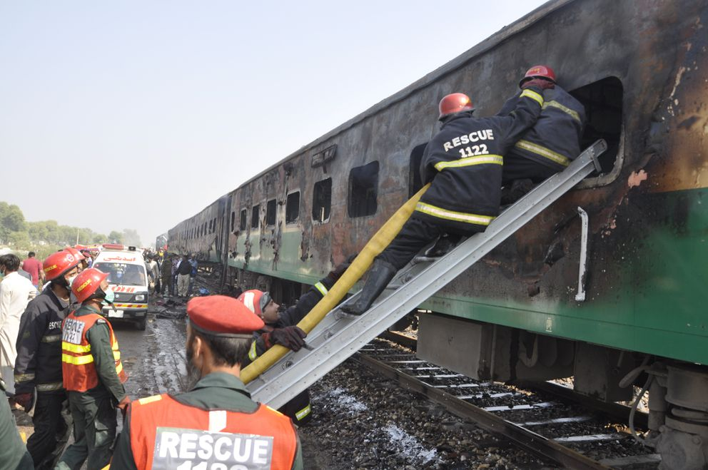 Rescue workers look for survivors following a train damaged by a fire in Liaquatpur, Pakistan, Thursday. (AP Photo/Siddique Baluch)