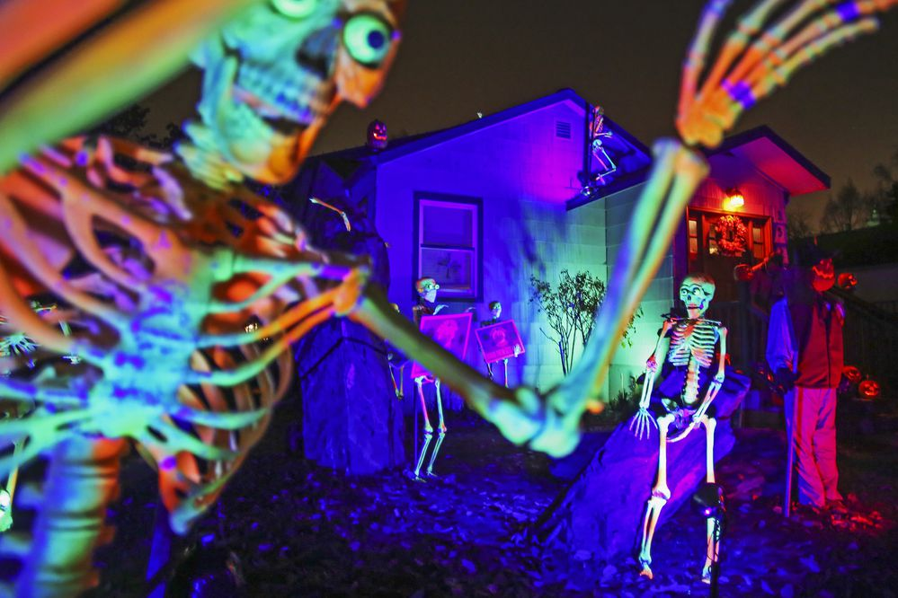 Moving skeletons, constructed from windshield wipers, individually carved foam pumpkins and orange lights decorate the outside of Owen Carey's home near W. 15th Avenue and H Street in Anchorage on Oct. 28, 2020. (Emily Mesner / ADN)
