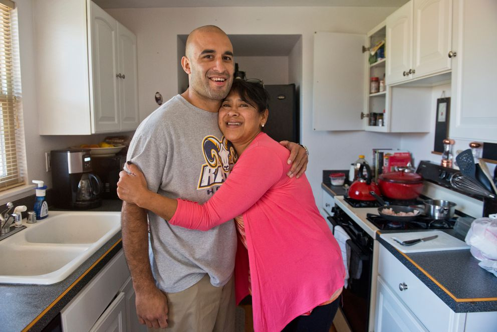 Scott Gomez gets a hug from his mother, Dalia, at home on Tuesday. (Marc Lester / Alaska Dispatch News)