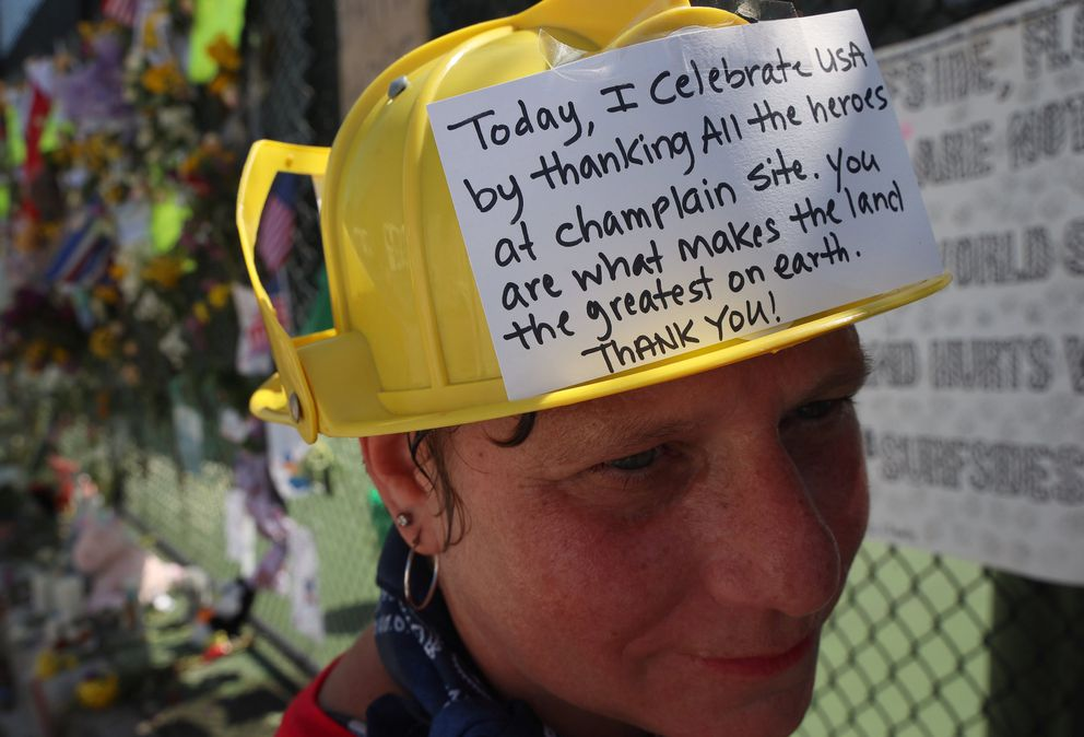 Hialeah resident Alison Kairuz ponders for a moment after pinning her handmade sign to the fence in support of families and friends who lost loved ones, at the memorial site on Sunday, July 4, 2021 in Surfside, Florida. (Carl Juste/Miami Herald/TNS)
