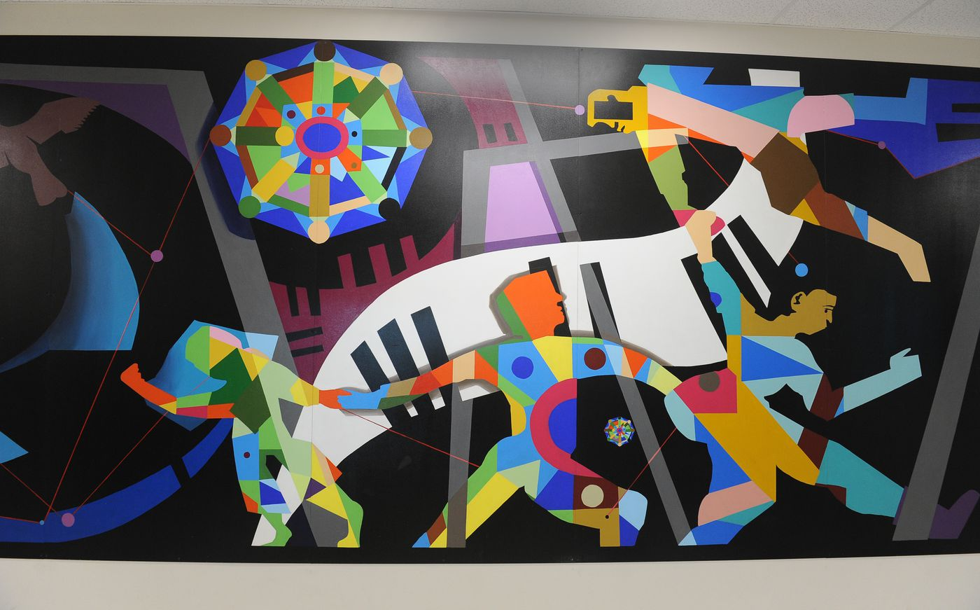 """Ethnounis Portal,"" a mural created by Marino-Heidel Studios, is mounted on a wall in Romig Middle School in Anchorage on July 7. The mural is part of Anchorage's 1% for Art program. (Bob Hallinen / ADN)"