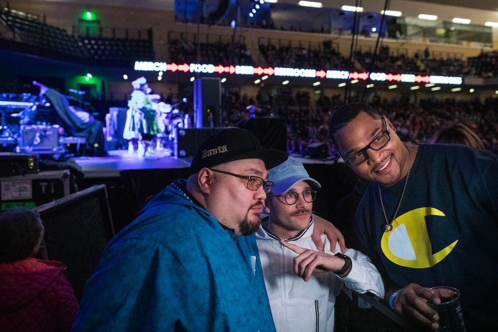 Dennis Davis, left, and Craig Moore, right, take a photo with Portugal. The Man singer John Gourley during the opening performance for Portugal. The Man's show Friday, Oct. 26, 2018 at the Alaska Airlines Center. The Acilquq traditional dance group opened for the band. (Loren Holmes / ADN)
