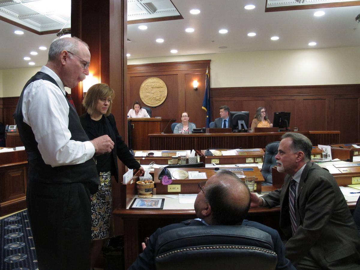 From left, Alaska Sens. Bert Stedman, Mia Costello, Lyman Hoffman and Peter Micciche speak during a break on the Senate floor on Tuesday, June 4, 2019, in Juneau, Alaska. (AP Photo/Becky Bohrer)