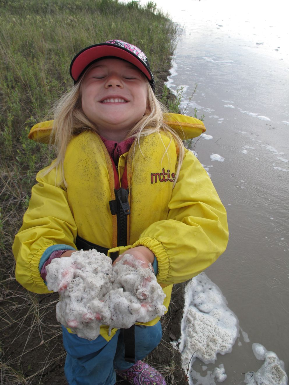 A girl examines foam floating on the Tanana River. (Ned Rozell / UAF Geophysical Institute)