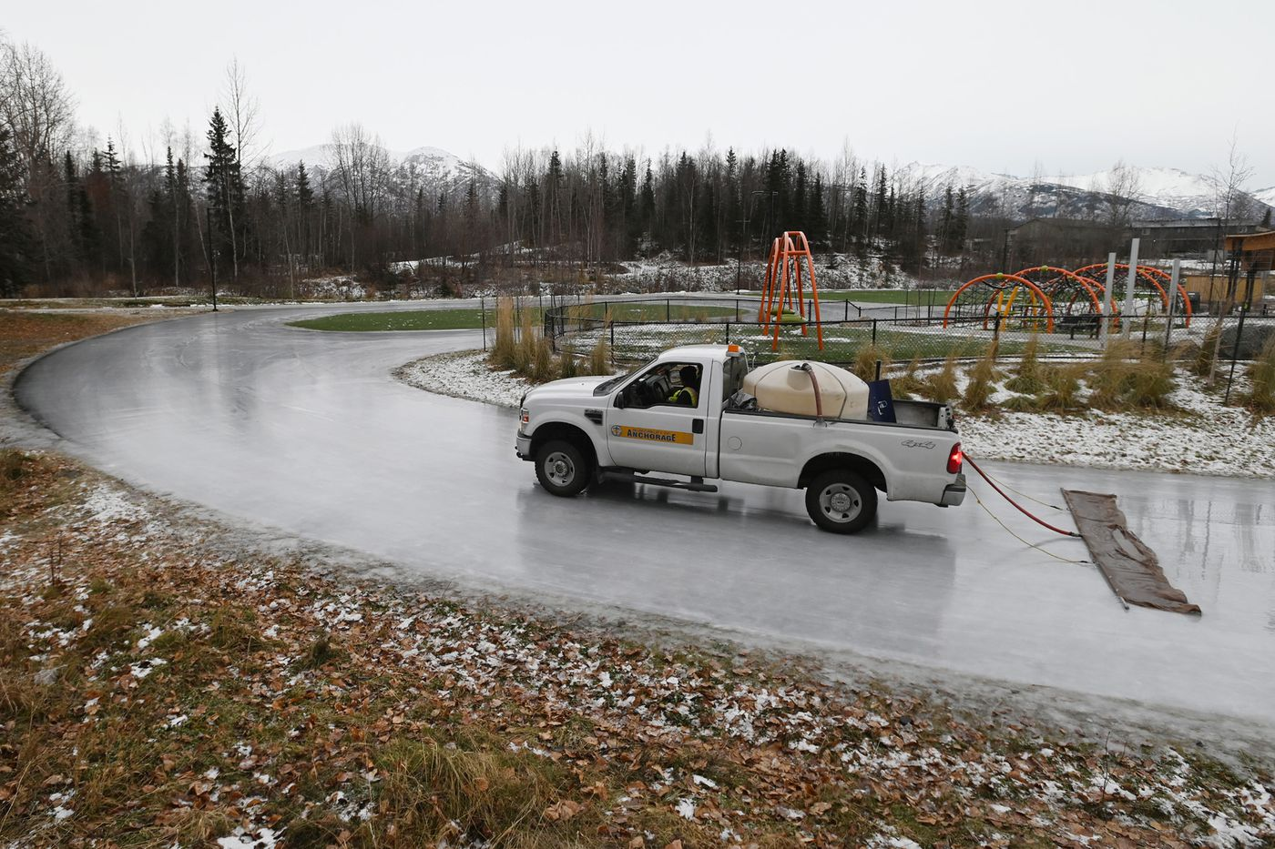 Municipality of Anchorage Parks and Recreation workers hot mopped the ice skating surface at Chanshtnu Muldoon Park on Thursday, Nov. 5, 2020. (Bill Roth / ADN)