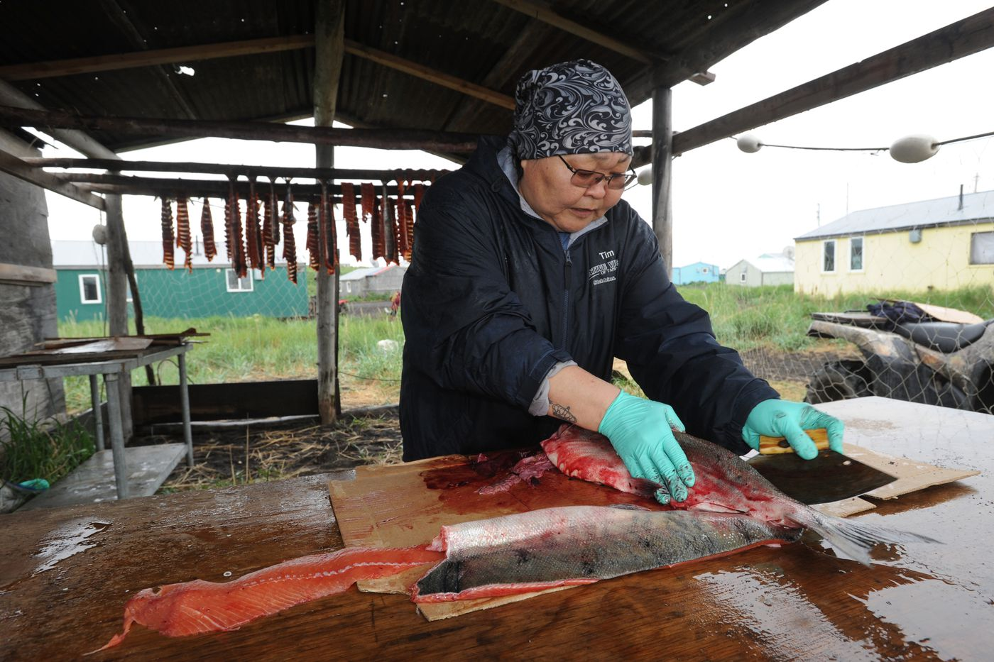Tania Snowball cuts up salmon after a day working as the village health aide. As a first responder who relies on village police officers to handle emergencies at her side, Snowball said she couldn't do her job without the local village police officers. (Bill Roth / ADN)