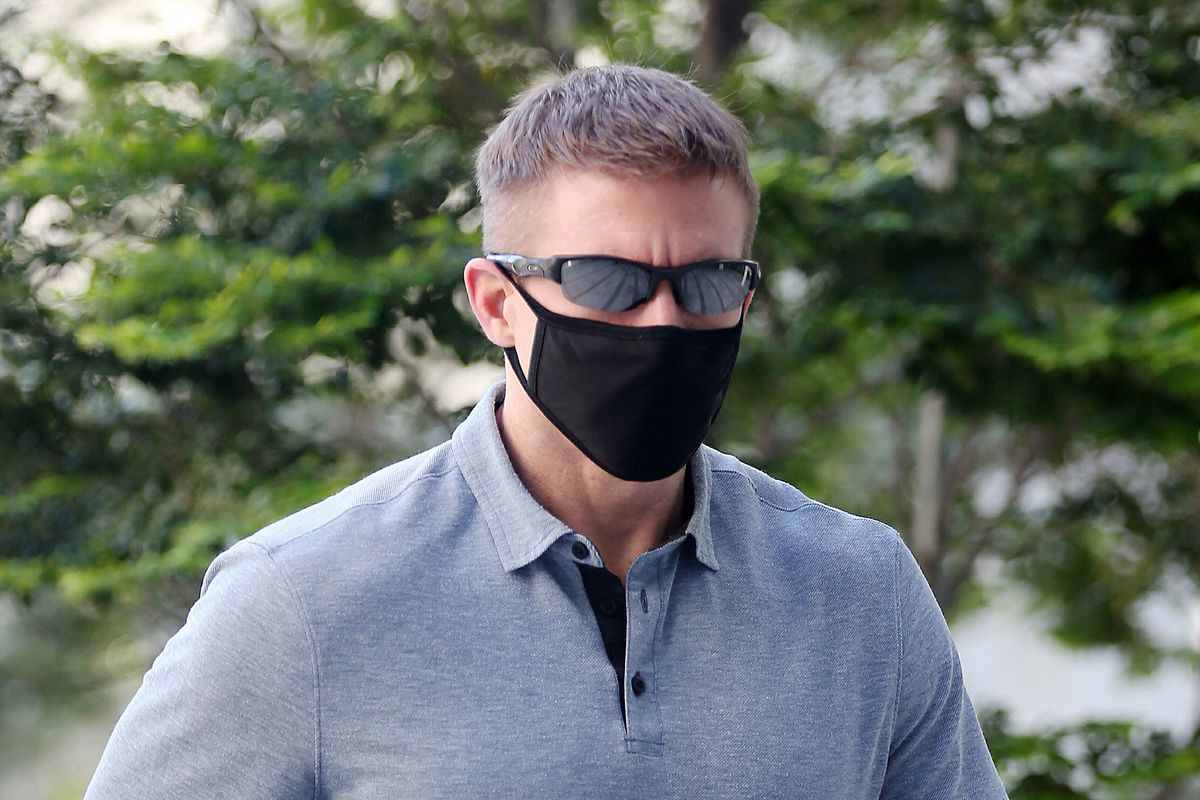 In this May 13, 2020, photo, Brian Dugan Yeargan, wearing a face mask and sunglasses, walks outside the Singapore State Court in Singapore. The 44-year-old American pilot has been jailed for four weeks for breaching a quarantine order in Singapore. Local media reported that Brian Dugan Yeargan was sentenced by a court Wednesday, May 13 for leaving his hotel room for three hours to buy masks and a thermometer. (The Strait Times via AP)