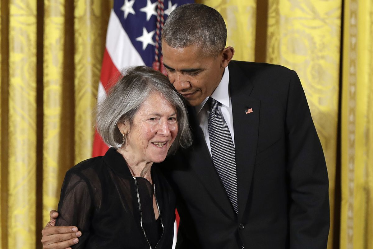 """President Barack Obama embraces poet Louise Gluck before awarding her the National Humanities Medal during a ceremony in the East Room of the White House, in 2016. The 2020 Nobel Prize for literature has been awarded to Gluck """"for her unmistakable poetic voice that with austere beauty makes individual existence universal."""" (AP Photo/Carolyn Kaster, File)"""