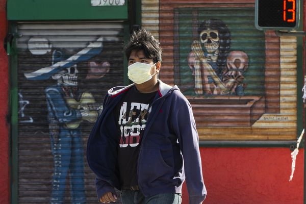 A pedestrian wears a face mask in the Boyle Heights area of Los Angeles on Wednesday, April 1, 2020. Los Angeles Mayor Eric Garcetti has recommended that the city's 4 million people wear masks when going outside amid the spreading coronavirus. Garcetti on Wednesday said people in the nation's second-largest city who are performing essential tasks such as food shopping should wear homemade, non-medical face coverings, or even bandannas. (AP Photo/Damian Dovarganes)