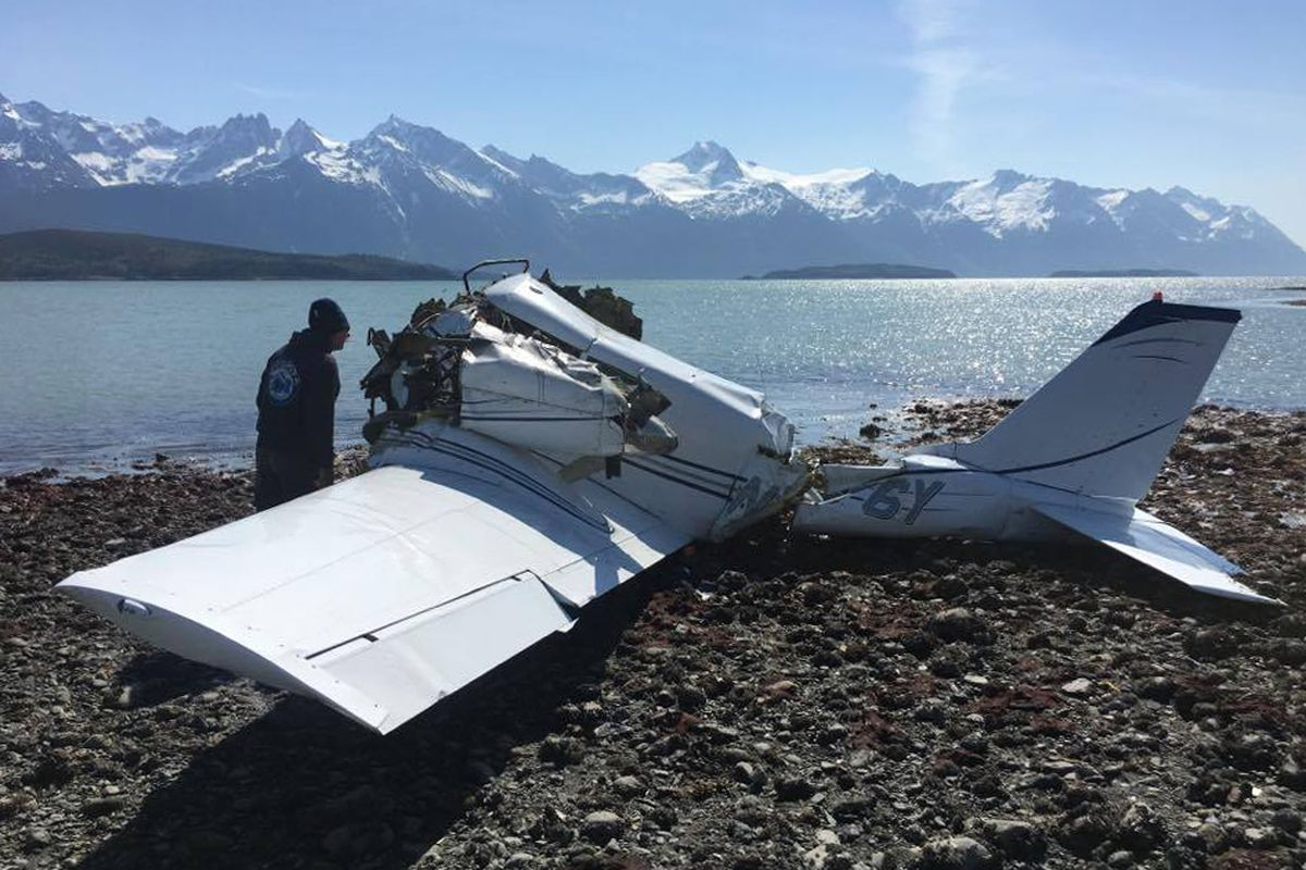 Tom Faverty peers into the wreckage of a Piper Comanche that crashed on the shore south of Haines on Saturday, May 27. As the tide came in, Faverty, wife Patricia, son Kirby, friend Steve Dice and tour guide Wiley Betz struggled to keep the plane afloat and crash survivor Chan Valentine, trapped inside the wreckage, above water. (Photo courtesy Patricia Faverty)