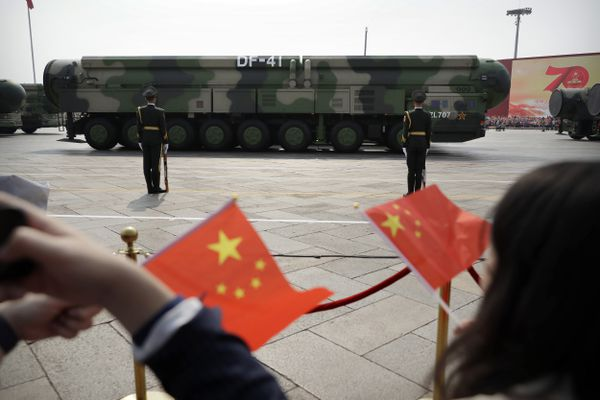 FILE - In this Oct. 1, 2019, file photo spectators wave Chinese flags as military vehicles carrying DF-41 ballistic missiles roll during a parade to commemorate the 70th anniversary of the founding of Communist China in Beijing. Trucks carrying weapons including a nuclear-armed missile designed to evade U.S. defenses rumbled through Beijing as the Communist Party celebrated its 70th anniversary in power. China appears to be moving faster toward a capability to launch its newer nuclear missiles from underground silos, possibly to improve its ability to respond promptly to a nuclear attack, according to an American expert who analyzed satellite images of recent construction at a missile training area. (AP Photo/Mark Schiefelbein, File)