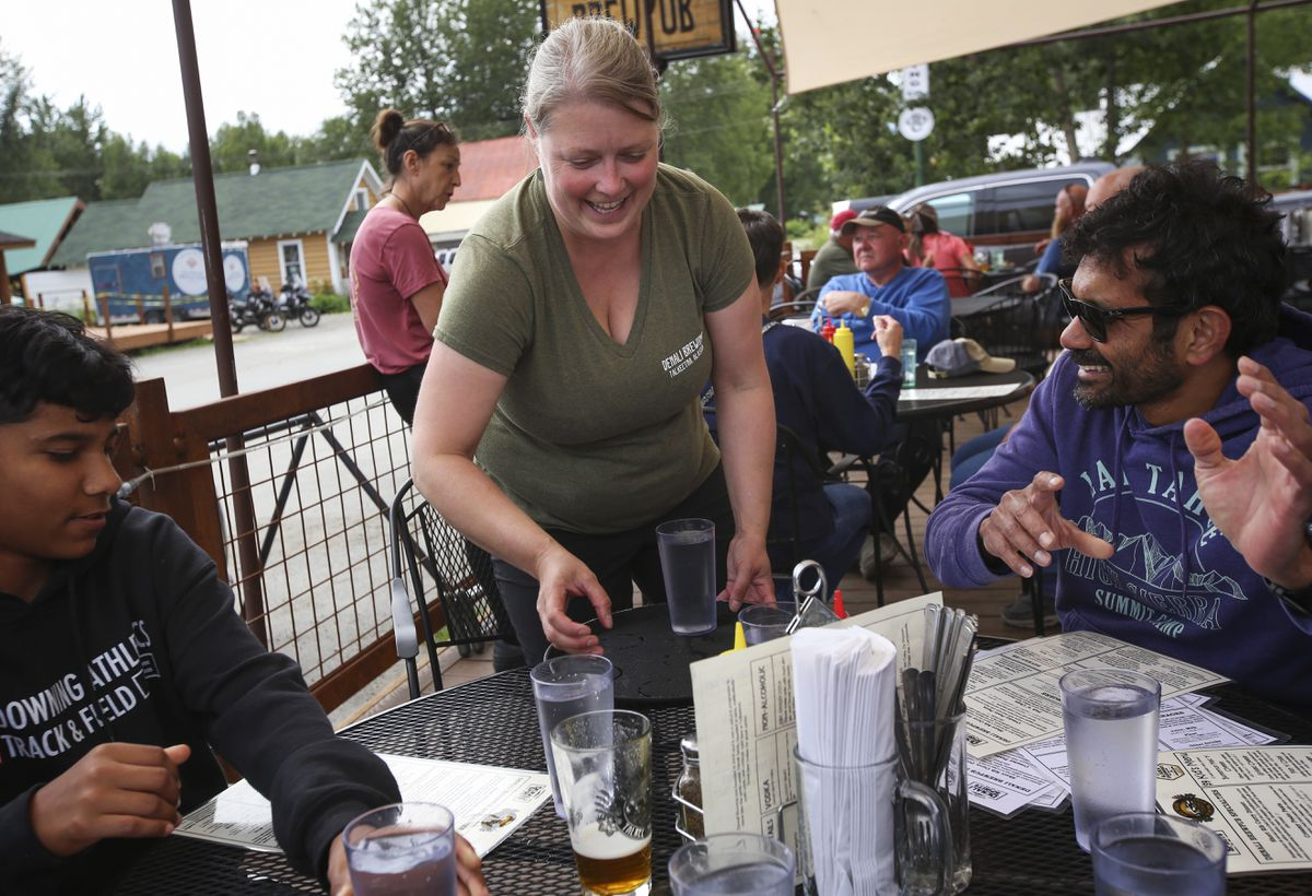"""Heidi LaFleur, Denali Brewpub's HR director, brings glasses of water to a table of people at Denali Brewpub in Talkeetna on Wednesday, July 14, 2021. """"I've been working the host stand quite a bit,""""she said. """"Our kitchen is short-handed, and our front of house is short-handed."""" (Emily Mesner / ADN)"""