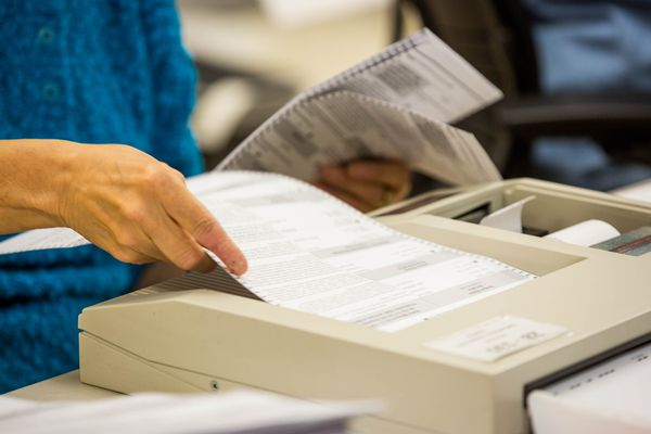 Review Accu-Vote Board member Dee Bowns feeds early voting ballots into a tally machine at the state Region II Division of Elections office in Anchorage on Tuesday, November 11, 2014. (Loren Holmes / ADN)