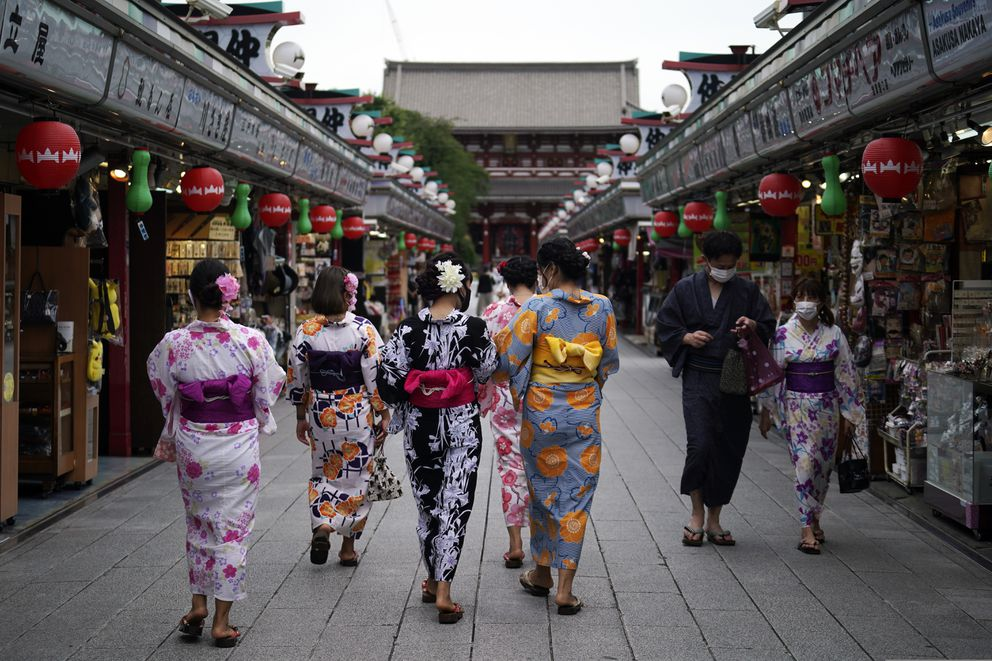 FILE - In this July 27, 2020, file photo, tourists in traditional Japanese kimonos walk in Asakusa district in Tokyo. Tourism operators across Asia and the Pacific are making furtive and faltering steps forward as well as some spectacular backward steps from the setback of the coronavirus pandemic that continues to ebb and surge across the globe. In Japan, new coronavirus outbreaks spread across the country with increasing travel during summer holidays. (AP Photo/Eugene Hoshiko)