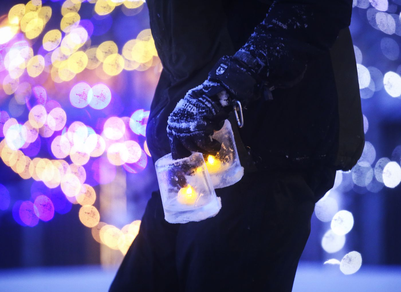 DECEMBER 20. Ryan Kenny, the Anchorage Museum Deputy Director of Exhibitions and Program Operations, carries two ice luminarias he made onto the front lawn of the museum in downtown Anchorage. (Emily Mesner / ADN)