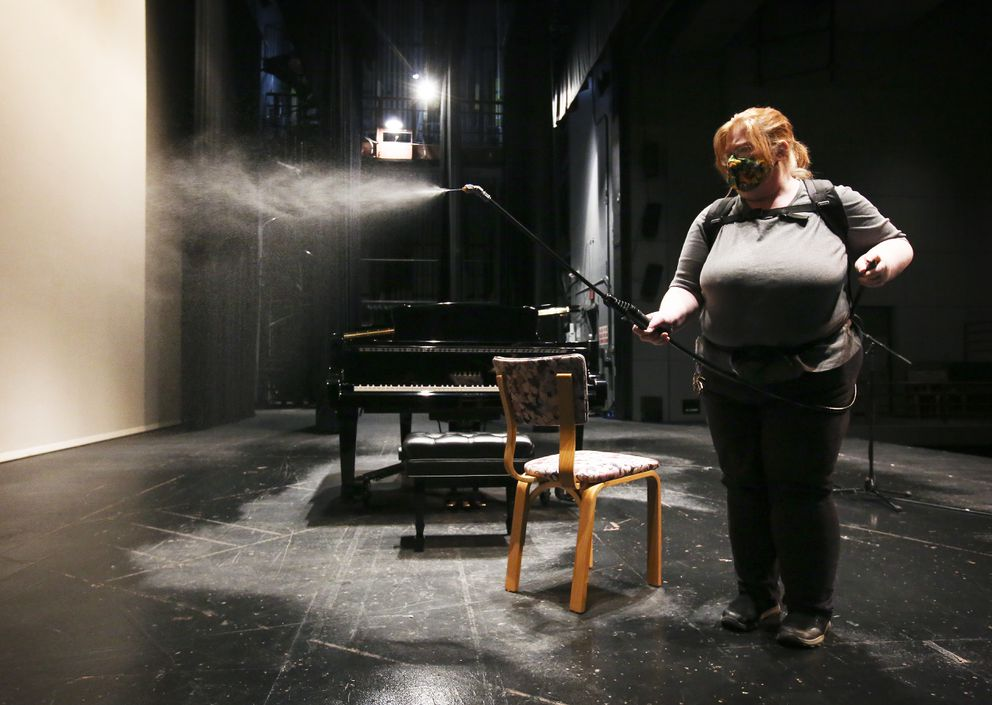 Wendy Odden sanitizes the theater's stage after performers recorded their pieces. (Emily Mesner / ADN)