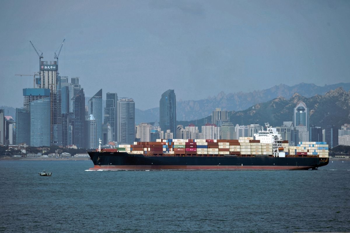 A container ship sails by the business district in Qingdao in east China's Shandong province. (Chinatopix via AP, File)