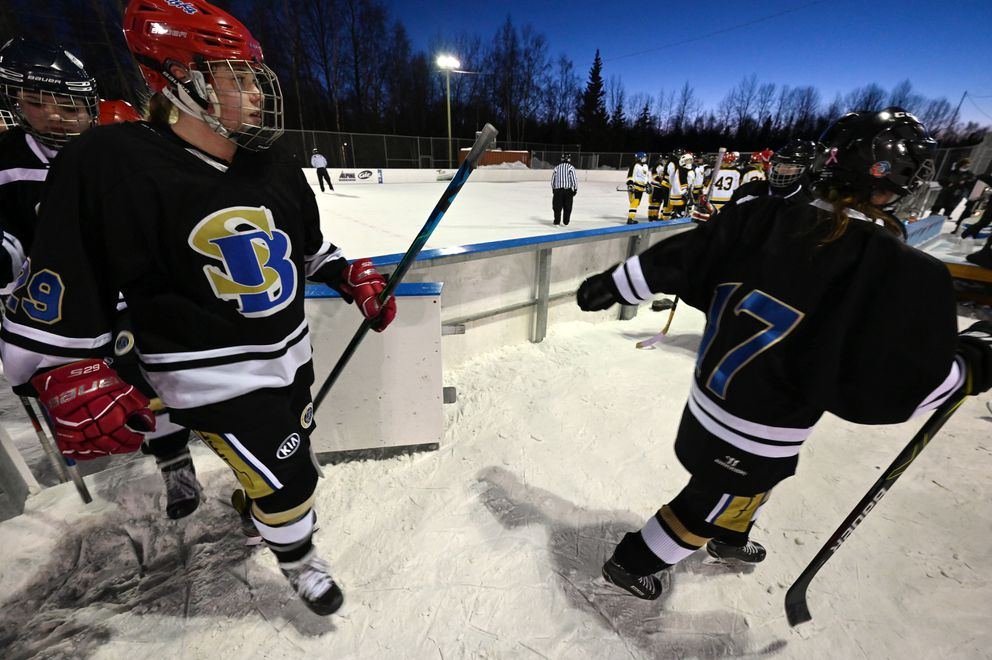 South/Bartlett players walk across the snow after defeating Dimond/West 2-0 in the first round of the girls high school hockey championships at the Bonnie Cusack Outdoor Ice Rinks on Monday, Feb. 1, 2021. (Bill Roth / ADN)
