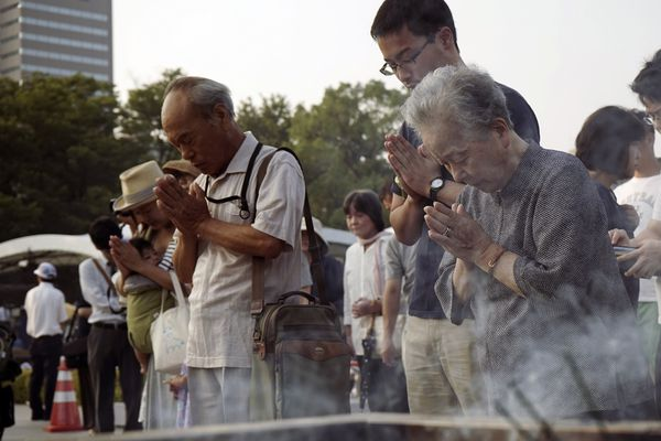 Visitors pray for atomic bomb victims in front of the cenotaph at the Hiroshima Peace Memorial Park in Hiroshima on Thursday as Japan marked the 70th anniversary of the atomic bombing of Hiroshima.