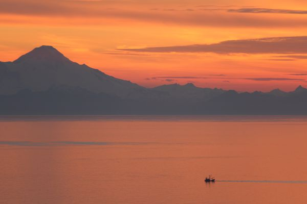 Mount Iliamna looms above a small fishing boat on Kachemak Bay. (Ground Truth Trekking)