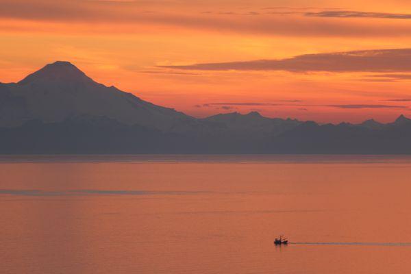 Mount Iliamna looms above a small fishing boat on Kachemak Bay. (Ground Truth Trekking)