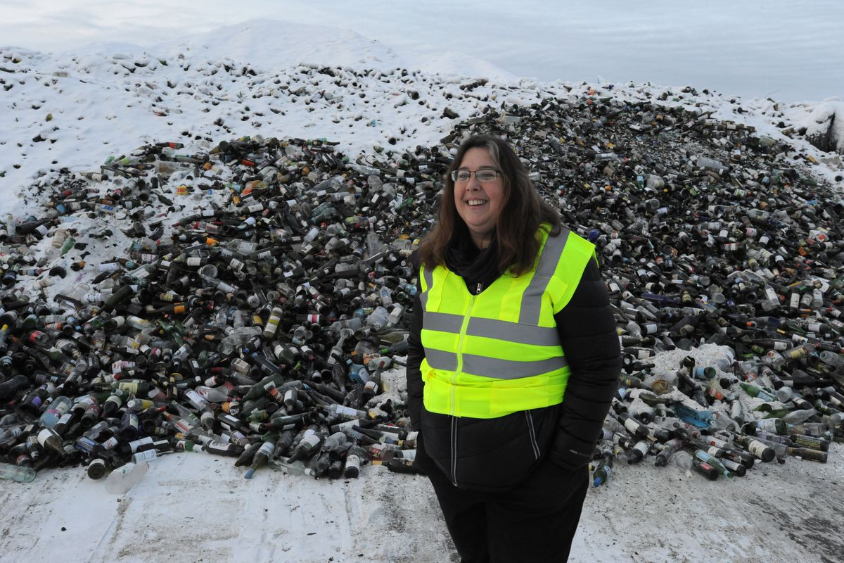 Environmental engineer Donna Mears stands near a mountain of glass bottles on Thursday, Dec. 29, 2016, that will be recycled at Central Recycling Services Inc. in Anchorage. The company collects 1,200 to 1,400 tons of glass each year and sold 300 tons of recycled glass aggregate in 2016. (Bill Roth / Alaska Dispatch News)