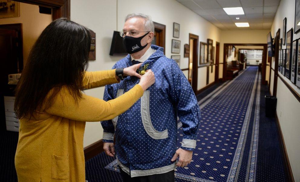 Amory Lelake pins a boutonniere to the lapel of Rep. Bryce Edgmon, I-Dillingham before the 32nd Alaska State Legislature convenes on Tuesday, Jan. 19, 2021. (James Brooks / ADN)