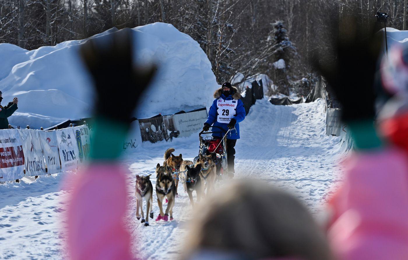 Matthew Failor arrives at the Iditarod finish line in Willow to cheers from Iditarod veteran DeeDee Jonrowe on March 16, 2021. (Marc Lester / ADN)